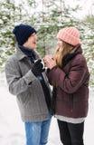 Gladlynta par med varma drinkar i frostig skog Royaltyfri Bild