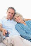 Gladlynta par på deras hållande ögonen på tv för soffa Royaltyfri Foto