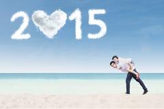 Gladlynta par på ryggen på stranden arkivfoton