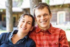 Gladlynta par som framme sitter av ett nytt hus Arkivbild