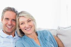Gladlynta par som kopplar av på deras soffa arkivbilder