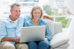 Gladlynta par som kopplar av på deras soffa genom att använda bärbara datorn Arkivbilder