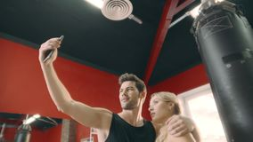 Gladlynta par som kramar för mobil selfie i konditionidrottshall stock video