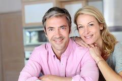 Gladlynta par som ler i köket Arkivbild
