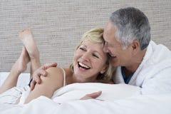 Gladlynta par som ligger i säng Royaltyfri Fotografi