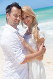 Gladlynta par som omfamnar och poserar på stranden på en solig dag Arkivfoto