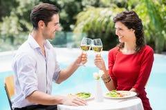 Gladlynta par som rostar vitt vin Arkivfoto