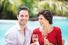 Gladlynta par som rymmer vitt vin Fotografering för Bildbyråer