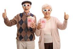 Gladlynta pensionärer med exponeringsglas 3D och popcorndanande tummar upp Royaltyfria Foton