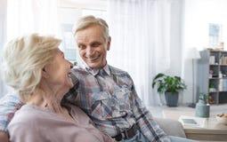 Gladlynta pensionärer som sitter i omfamning royaltyfri fotografi
