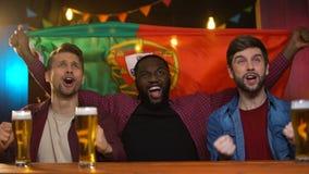 Gladlynta portugisiska blandras- män som firar segern för fotbolllag, vinkande flagga lager videofilmer