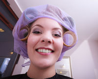 Gladlynta roliga blonda flickapapiljottrullar vid haidresser i skönhetsalong Fotografering för Bildbyråer