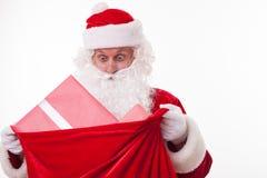 Gladlynta Santa Claus bär en påse av gåvor arkivbilder