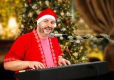 Gladlynta Santa Claus som spelar pianot och att sjunga Royaltyfria Bilder