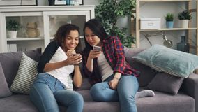 Gladlynta studenter asiat och afrikansk amerikan är tala och skratta se smartphoneskärmen genom att använda att sitta för grejer stock video