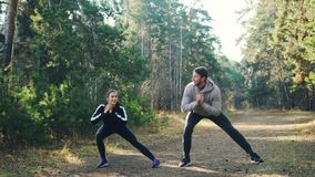 Gladlynta studenter gör sportar tillsammans parkerar in squatting och att le tycka om övningar och naturen Man och kvinna arkivfilmer