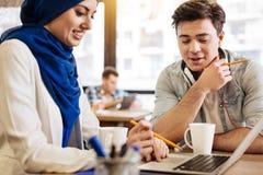 Gladlynta studenter som använder bärbara datorn för att studera Arkivbild