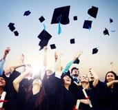 Gladlynta studenter som kastar avläggande av examenlock i luften royaltyfri fotografi