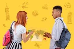 Gladlynta studenter som studerar geografi och innehavet en översikt av världen arkivfoton