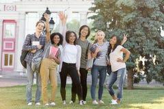 Gladlynta studenter som utomhus står och vinkar royaltyfria foton