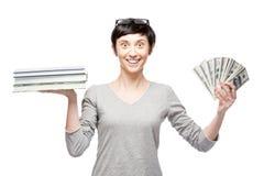Gladlynta tillfälliga kvinnainnehavböcker och pengar royaltyfria foton