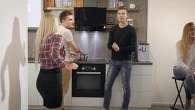 Gladlynta tonårs- pojkar och flickor har gyckel på ett kök i lägenhet i aftonen som dricker vin