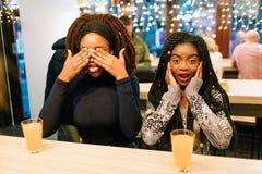 Gladlynta trevliga unga afrikanska kvinnor sitter på tabellen och att ha gyckel Första räkningsögon med händer Håll i andra hand  royaltyfri bild