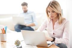 Gladlynta två arbetare skriver på datorer royaltyfri foto