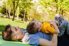 Gladlynta två bröder ligger på gräset i parkera och spelar i roliga lekar royaltyfri foto