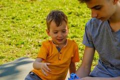 Gladlynta två bröder ligger på gräset i parkera och spelar i roliga lekar arkivbilder