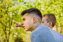 Gladlynta två bröder ligger på gräset i parkera och spelar i roliga lekar fotografering för bildbyråer