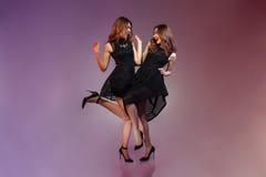 Gladlynta två kvinnor i nattsvartklänning Arkivfoton