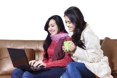 Gladlynta två kvinnor som direktanslutet shoppar Royaltyfria Foton