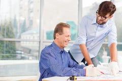 Gladlynta två manliga teknikerer som diskuterar nytt projekt Arkivfoto
