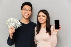 Gladlynta unga asiatiska älska hållande pengar för par och visningskärm av mobiltelefonen arkivbild