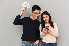 Gladlynta unga asiatiska älska pengar och mobiltelefon för par hållande fotografering för bildbyråer