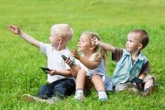 Gladlynta unga barn som spelar i parkera Fotografering för Bildbyråer