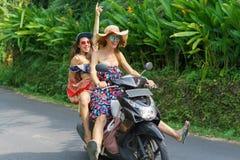 gladlynta unga kvinnor som rider mopeden på soligt royaltyfri foto