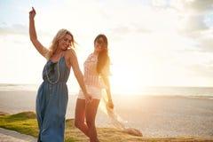 Gladlynta unga kvinnor som tycker om och dansar på en strand arkivfoto
