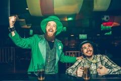 Gladlynta unga män sitter på stångräknaren, i bar och att hurra De håller ögonen på framåtriktat Grabbar har rånar av öl på stång royaltyfria foton