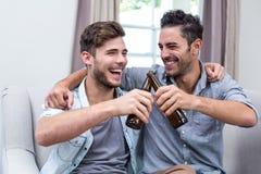 Gladlynta unga manliga vänner som hemma rostar öl Arkivbild