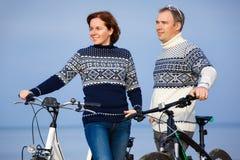 Gladlynta unga par som utomhus cyklar på stranden arkivbild