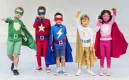 Gladlynta ungar för Superheroes som uttrycker Positivitybegrepp arkivfoto