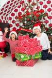 Gladlynta ungar med många julgåvor Arkivbilder