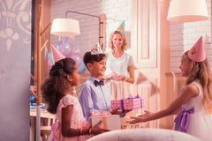 Gladlynta ungar som ler och ger gåvor till den lyckliga flickan royaltyfria foton