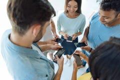 Gladlynta ungdomarsom använder deras smartphones Arkivbilder