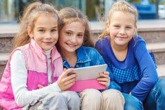 Gladlynta vänner med en elektronisk minnestavla arkivfoton