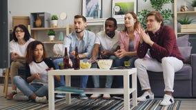 Gladlynta vänner som använder smartphones som håller ögonen på TV och talar därefter diskutera nyheterna stock video