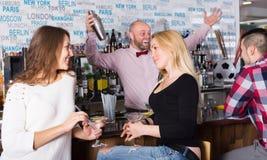 Gladlynta vänner som dricker och pratar Royaltyfria Bilder