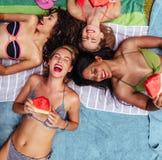 Gladlynta vänner som ligger vid poolsiden med vattenmelon royaltyfri foto